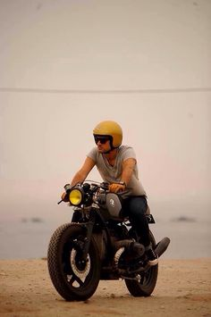 Man. Motorbike. Custom. Cafe racer. Gold helmet. Beach. Manly. Lone wolf. T-shirt and jeans.