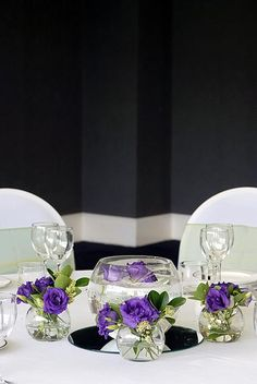 Fishbowl vases with purple lisianthus for a wedding table centre