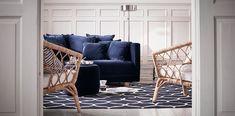 2-pers. sofa med betræk af mørkeblå velour og masser af puder, vist sammen med en puf med samme betræk og 2 lænestole af rotting.