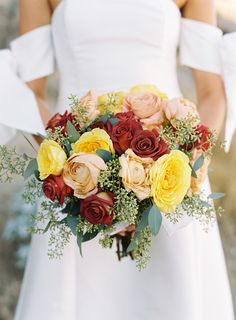Artisan Event Floral Décor used beautiful autumnal shades in this bouquet. Blush garden roses, salmon ranunculus, dark-red tea roses, and seeded eucalyptus were tied with a white bow.