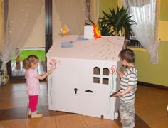 Children paint the cardboard house