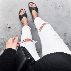 Ripped white denim with black flat sandals and black sweater.