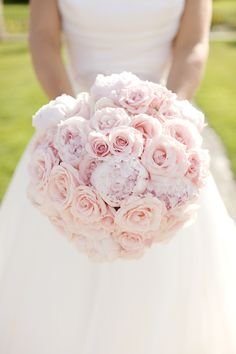 A unique domed hand tied bouquet of light pink sweet avalanche roses, small pink majolica garden roses , light pink peonies festiva maxima . hand tied bridal bouquet from pollen flowers brighton