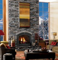 i love the glass walls and the massive fireplace... perfect for a house nestled by the mountains.