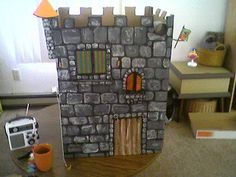 DIY Cardboard castle: Hand painted with working drawbridge (using string) and windows that open and close. The turret was made with a paper towel roll and funneled construction paper for the top. My oldest son and I made this 3 years ago and he still plays with it! Goes perfect with Playmobil characters!