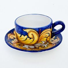 Coffee cup & saucer with gold leaves on a white background with a blue border.