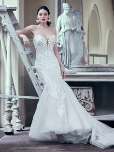 This glamorous fit-and-flare wedding gown features a bodice of lace motifs and sheer detailing, drifting into a tulle skirt trimmed in horsehair. Beaded lace motifs adorn the illusion plunging sweetheart neckline, while beaded spaghetti straps glide into a sheer back accented in lace motifs. Finished with covered buttons over zipper closure.