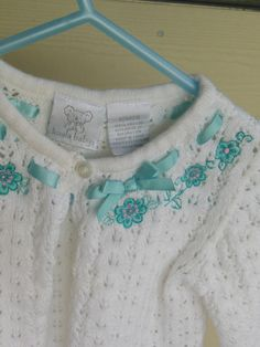 Vintage baby clothes. White baby sweater with teal flowers and bow. One button at top for fastening. on Etsy, $20.00