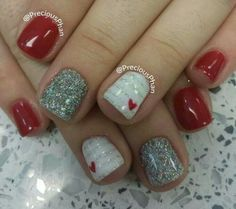 Red nails with accenting silver glitter nail and white nails with a small heart. Cute for valentines day