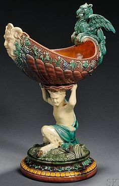 Continental Majolica Figural Compote, 19th century, the boat-form bowl mounted with a griffin handle and Bacchanalian mask spout with fruiting grapevine border, supported atop a scantily clad satyr seated on a rock amongst waves on a stepped circular base, ht. 15 5/8 in. Cute Teapot, Italian Renaissance, Pottery Making, Glazes For Pottery, China Patterns, Muted Colors, Ceramic Art, Vintage Antiques, Art Decor