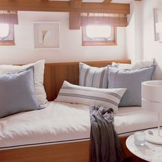 Stylish at Sea    The varnished wood cabin of Michael Lee's yacht, Dakota, is all about understated glamour. The cozy berth serves as a guest room; nautical striped pillows from West Elm and linen shams from Williams-Sonoma Home complete the look.
