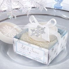 Shop Let it Snow scented snowflake soaps packaged atop a bed of natural raffia in an icy blue and white gift box tied with a hanging snowflake gift tag.