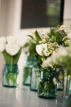 Floral arrangements in vintage blue mason jars.    Cate Jackson Photography www.catejacksonphoto.com