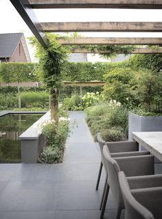 De nieuwbouwtuin krijgt extra sfeer door de strakke leibomen en exclusieve pergola