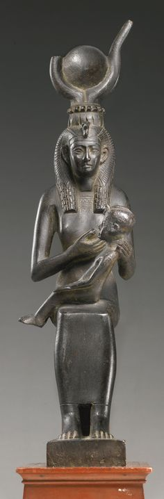 An Egyptian Bronze Figure of the Goddess Isis with Horus, 26th Dynasty, 664-525 B.C. of slender form seated with her feet resting on a trapezoidal footstool, her son Horus in her lap, and wearing a long close-fitting dress, engraved broad collar, echeloned tripartite wig, vulture headdress, and diadem of uraei surmounted by horns and sun-disk, her face with lips rounded at the corners, large eyes with finely incised folds on the upper lids, and incised tapering eyebrows. Height without tenon…