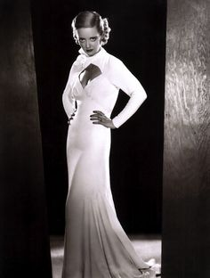 "Bette Davis wearing a ""cut-out"" bodice, evening dress.......cut-outs are trending again now!! Note the sheath skimming fit with soft folds at the maxi hem."