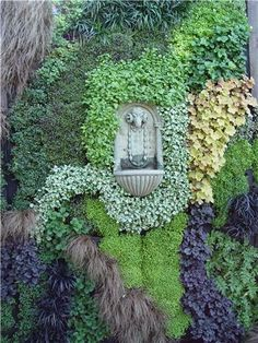 This French-inspired wall fountain is placed within a lavishly-planted vertical garden. Photo by Maureen Gilmer.