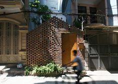 A perforated brick screen shields a verdant courtyard at the entrance to this…