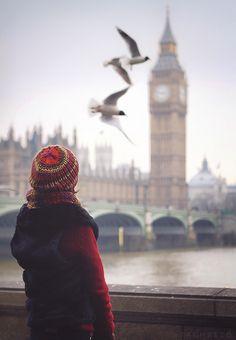 Muchacha joven con un abrigo rojo y sombrero de lana roja ve cómo dos gaviotas sobrevuela el Támesis. Al fondo, el Big Ben