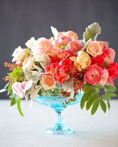 Tulipina shares how to create this romantic centerpiece featuring pepper berries, spray roses, and godetias.