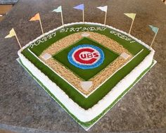 """Chicago Cubs Birthday Cake - My sister wanted a Cubs birthday cake for my nephew. I started with a 16"""" x 16"""" square cake and cut the baseball field from that.  Cake is marble with BC icing.  The word """"Cubs"""" and the bases are made out of fondant with crushed gram crackers for the sand."""