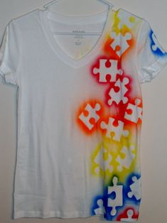 Lay down big puzzle pieces and spray paint over them. Wait until they dry to take the off (the picture is from etsy only that I find the instructions for this great tshirt idea :D )