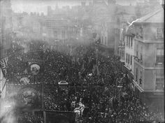 Broad Street, Reading, looking westwards from the crossing of Minster Street and the Butter Market, 4th November 1891. Crowds at the unveiling of the statue of George Palmer, with a procession of banners down the south side of the street. 1890-1899 : glass negative by H. W. Taunt, Box 22 No. 8004.