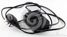 A closeup of a camera battery in a charger, isolated on white. Headset, Charger, Headphones, Tools, Headpieces, Headpieces, Hockey Helmet, Appliance, Utensils
