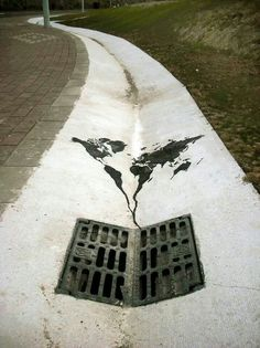 world going down the drain. street art