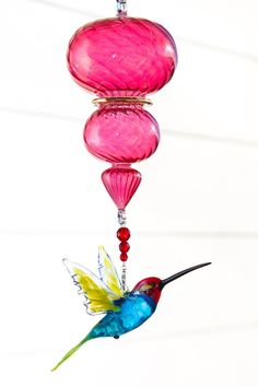 Red Headed Hummingbird with Handblown Red Spiral Suncatcher Ornament. This handmade glass lampwork Red Headed Hummingbird is a great addition to any home window or indoor bird house. Simply hang anywhere and enjoy the sparkles! Comes beaded with crystal and a Spiral Handblown Glass Ornament. the total length is 10 inches with the Red Headed Hummingbird being 3.5 inches wide by 2.5 inches long. This is a great gift for anyone who loves their garden and/or loves looking at Red Headed...