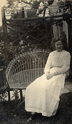 Edwardian lady sits on wire garden seat...