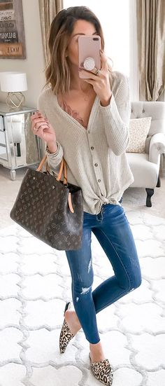 #spring #outfits woman wearing white button-up blouse, blue denim jeans, and brown leopard-print mule shoes while holder iPhone and brown Louis Vuitton handbag. Pic by @kateireneblue