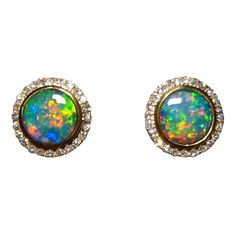 A stunning pair of Opal and Diamond stud earrings in 14k Yellow Gold. The round Lightning Ridge Opals having a unique play of color and are very bright.
