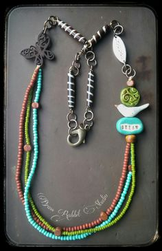 """Long boho necklace with ceramic bird by Kylie Parry, ceramic """"dream"""" bead by Diane Hawkey, ceramic decorative green coin by Panjego Art House, pewter leaf connector by Green girl studios that reads """"love life"""" on back side, seed beads, wood beads, wooden butterfly connector, Vintaj brass branch charm and chain, swirl pattern bone beads, and large brass lobster clasp."""