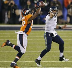 Super Bowl XLVIII - Russell Wilson flips a pass to avoid being sacked by outside linebacker Danny Trevathan. Seattle did allow a sack all night.  Read More: http://sportsillustrated.cnn.com/nfl/photos/1402/si-best-photos-from-super-bowl-xlviii//11/#ixzz2sJhYnm2M