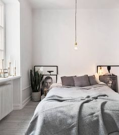Bedroom: pale grey limewashed timber floorboards, white walls with mouldings, cactus in cloth bag on floor, picture frames with black-and-white photography on floor, light and dark grey bed linen, exposed lightbulb pendant light