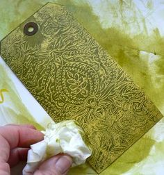 emboss waxed paper, then sandwich it between tags or cardstock, dry iron, rub with ink pad then use baby wipe to remove ink from waxy areas