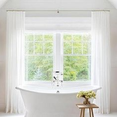A white vintage roll top bathtub with a chrome tub filler sits beneath windows covered in white sheer curtains and is matched with a wooden bath table and a striped French burlap rug. Grey Bathroom Cabinets, Grey Bathrooms, Country Bathrooms, White Bathroom, French Bathroom, Master Bathroom, Master Baths, Vintage Bathtub, New England Farmhouse