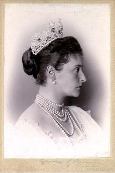 Alexandra is wearing the tiara from a sapphire parure made by Friedrich Koechli and given to her by Tsar Alexander III and Tsarina Marie Feodorovna. Intertwined scrolls in which 16 sapphires are set mounted in gold; the diamonds are mounted in silver and linked with gold.
