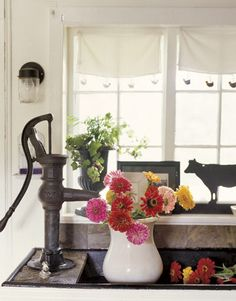 Hand-Pump Faucet -- At this kitchen sink, the faucet is an iron hand pump that dates to the late 1800s; the farmhouse's owner tiled the backsplash in slate. Filtering light from the window is a curtain that's actually a dishtowel edged in crocheted hens and chicks.