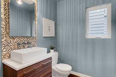 Gorgeous tiling for bathroom backsplash. Dark espresso-stained wood vanity. Beautiful green home by LimeLite Development.