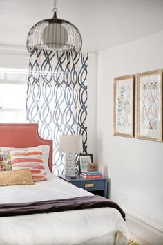 Bed in front of window, bedside tables, lamps