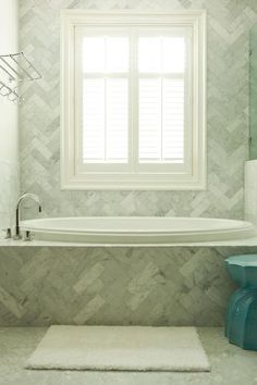 Stunning bathroom features a marble herringbone tiled tub alongside a marble herringbone surround flanked by a train rack to the left and a walk-in shower to the right.