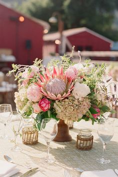 So much #rustic in this photo! <3 the floral centerpiece, candle holders, and of course the barns in the back! @merrylbrown