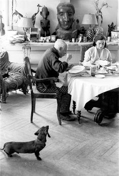 """Lump and Picasso meet for the first time. Mutual love."" [Lump approaching the table where Picasso and Jacqueline are eating. Villa La Californie, 1957.] The Private World of Pablo Picasso, p. 3."