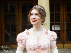 A pink silk Regency ball gown sewn entirely by hand and embellished with pearls, smocking, gathered lace, ribbon cockades, and ribbon rosettes.  Sewn by Edelweiss Patterns.