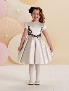 Short gathered sleeve satin and charmeuse knee-length dress with jewel neckline, bodice accented with unique contrasting embroidered motif, thin piped waistband features center front bow, pleated semi-circular skirt, perfect as a party dress, flower girl dress or girls holiday dress.Sizes: 2 – 14
