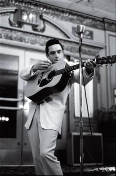 Johnny Cash and his most popular way of playing his guitar. The blonde in the pic.