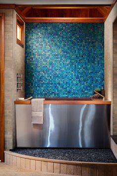 These glass mosaic tiles from Oceanside Glasstile create a gorgeous accent wall. The colors are reminiscent of cool blue Mediterranean waters, perfect for taking a long, relaxing soak. With such a strong decorative element on the wall, the room needs no other artwork or bold color to enhance it.