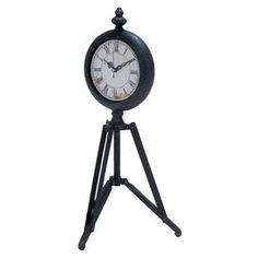"""Metal tripod table clock in black.   Product: ClockConstruction Material: MetalColor: Black and whiteDimensions: 17"""" H x 9"""" W x 9"""" DAccommodates: Batteries not includedCleaning and Care: Wipe with a dry cloth"""